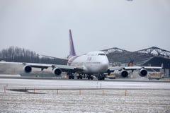Thai Airways International Boeing 747-400 HS-TGG in München-Flughafen, Winter Lizenzfreie Stockfotos