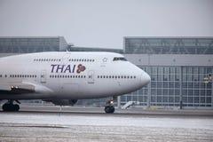 Thai Airways International Boeing 747-400 HS-TGG in München-Flughafen, Winter Lizenzfreie Stockbilder