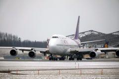 Thai Airways International Boeing 747-400 HS-TGG nell'aeroporto di Monaco di Baviera, inverno Fotografie Stock Libere da Diritti