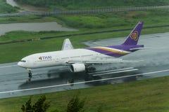 Thai Airways tar av den phuket flygplatsen på våt landningsbana Royaltyfri Fotografi