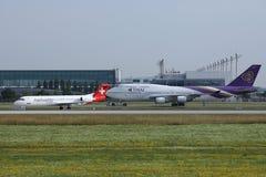 Thai Airways y Helvetic que llevan en taxi en el aeropuerto de Munich, MUC, vista delantera foto de archivo