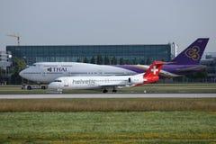 Thai Airways y Helvetic que llevan en taxi en el aeropuerto de Munich, MUC, vista delantera imagen de archivo libre de regalías
