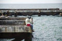 Thai angler or fisherman use fishing-rod fishing fish in the sea royalty free stock image