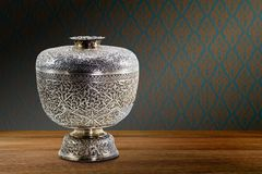 Thai antique ancient grunge silver bowl on wooden tabletop on vintage brown purple concrete wall background royalty free stock image
