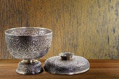 Thai antique ancient grunge silver bowl on wooden tabletop on vintage grunge wooden wall background Royalty Free Stock Images
