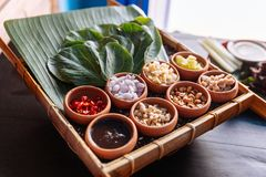 Thai appetizer called `Miang Kham`, some of nutritious snack wrapped in leaves with a sweet and salty sauce.  Stock Photos