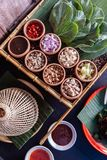 Thai appetizer called `Miang Kham`, some of nutritious snack wrapped in leaves with a sweet and salty sauce.  Stock Image
