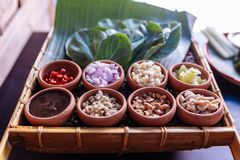 Thai appetizer called `Miang Kham`, some of nutritious snack wrapped in leaves with a sweet and salty sauce.  Stock Photo