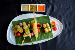 Thai appetizers spring rolls, crispy prawn, Thai sausage, chicken satay on black background. stock photo