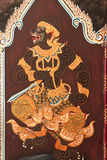 Thai art of Ramayana story on the door in Thai temple. Royalty Free Stock Images