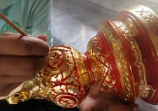 Thai Artist putting gold on red colour painted wooden carved knob Royalty Free Stock Photo