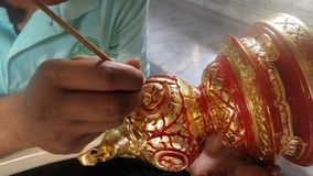 Thai Artist putting gold on red colour painted wooden carved knob Stock Photography