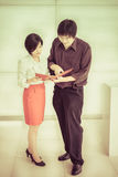 Thai (Asian) boss is ordering a task for his cute secretary in t Royalty Free Stock Photo