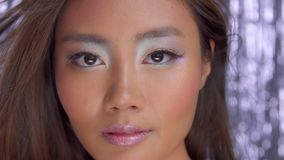 Thai asian model in studio with silver rain disco background and party makeup. Closeup of asian eye makeup uses rainbow holographic eyeshadows stock video footage