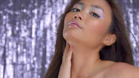 Thai asian model in studio with silver rain disco background and party makeup. Closeup portrait of asian model with ideal skin, wears rainbow highlight stock video footage