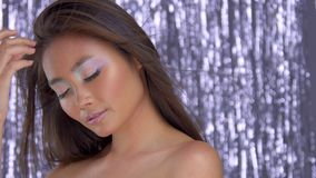 Thai asian model in studio with silver rain disco background and party makeup. Commercial portrait of asian model with disco party makeup on silver rain stock footage