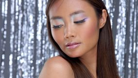 Thai asian model in studio with silver rain disco background and party makeup. Pretty asian young model with party makeup poses to a camera stock video