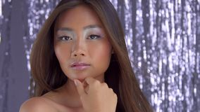 Thai asian model in studio with silver rain disco background and party makeup. Thai asian model in studio with silver rain disco background watching aside. ideal stock video