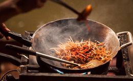 Thai Asian street fast food in hot pan, Pad Thai, or phad thai is a stir fried rice noodle dish commonly served as a street food Stock Image