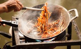 Thai Asian street fast food in hot pan, Pad Thai, or phad thai is a stir fried rice noodle dish commonly served as a street food Royalty Free Stock Photos