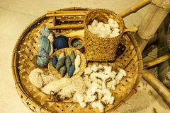 Thai asian traditional cultural indigo color dyeing silk cloth process textile tools; yarn , shuttles, spun, etc. on brown rattan. Wooden sieve basket. Local stock photo
