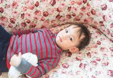 Thai baby boy laying on sofa because he feel tried Royalty Free Stock Photography