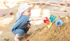 Thai baby boy palying on  pile of sand with toy Royalty Free Stock Photography