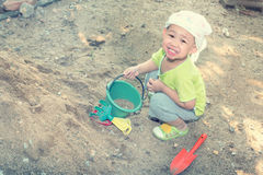 Thai baby boy palying on  pile of sand with toy and plastic fork Royalty Free Stock Images