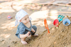 Thai baby boy palying on  pile of sand with toy Stock Image