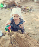 Thai baby boy palying on  pile of sand with toy Royalty Free Stock Image