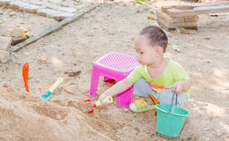 Thai baby boy palying on  pile of sand with toy Stock Images
