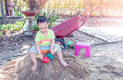 Thai baby boy palying on pile of sand with toy stock photo