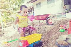Thai baby boy palying on  pile of sand with toy Stock Photography