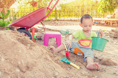 Thai baby boy palying on  pile of sand with toy and plastic fork Royalty Free Stock Image