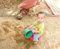 Thai baby boy palying on  pile of sand with toy and plastic fork Royalty Free Stock Photo