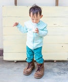 Thai Baby boy try to  wearing father& x27;s boots Royalty Free Stock Image