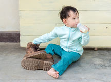 Thai Baby boy try to  wearing father& x27;s boots Royalty Free Stock Photo