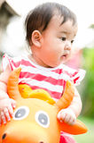 Thai baby. Cute Asia baby in sitting animal toy 'Thailand Stock Photo