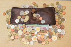 Thai baht coin and paper with brown leather wallet on plywood ba. Ckground stock image