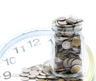 Thai Baht coins in jar with clock face Royalty Free Stock Image