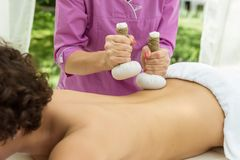 Thai Ball Massage. Woman in day SPA getting thai herbal compress massage. Royalty Free Stock Photos