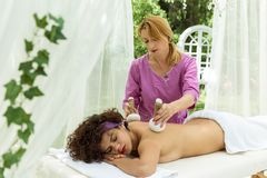 Thai Ball Massage. Woman in day SPA getting thai herbal compress massage. Stock Photo