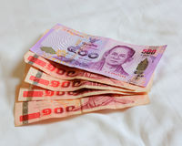 Thai bank note and Thai bank note on the bed sheet Royalty Free Stock Images