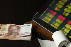 Thai banknote scene. The thailand currency banknote with tablet monitor screen shown the stock information graph represent the business and finance concept stock images