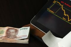 Thai banknote scene. The thailand currency banknote with tablet monitor screen shown the stock information graph represent the business and finance concept royalty free stock photography