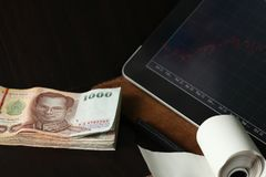 Thai banknote scene. The thailand currency banknote with tablet monitor screen shown the stock information graph represent the business and finance concept royalty free stock image