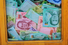 Thai banknotes money in the wooden donation box at the Buddhist Stock Images