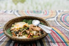 Thai Basil pork and egg near rice field. Rice with stir fried Basil pork and fried egg on natural dish and painted wooden table near Rice paddy field. Famous stock photo