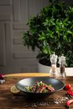 Thai beef salad in black plate on wooden background royalty free stock image