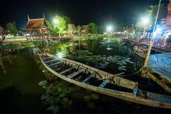 Thai boat wooden craft in night market. Thai boat wooden craft that floating in canal at night market Kanchanaburi, Thailand Stock Photo
